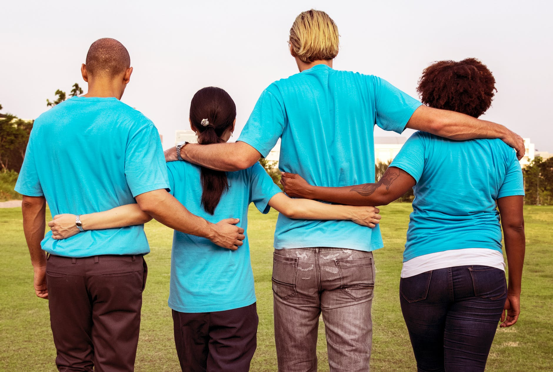 four people wearing blue crew neck t shirts